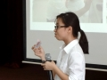 201608_招待研修旅行報告会 折鶴を見せながら報告をする学生